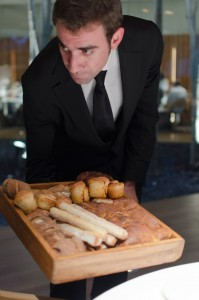 Handsome waiter offering bread